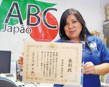 表彰状を手にする安富祖さん