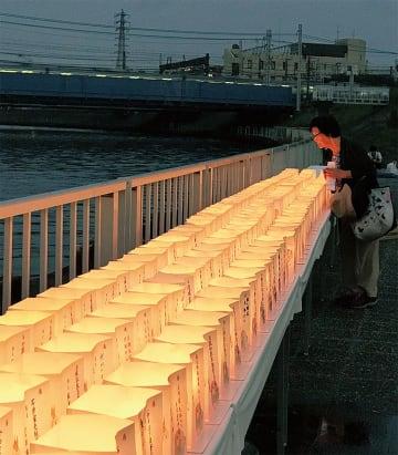 河川敷に並べられる灯ろう(同会提供)