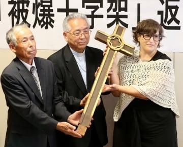マウス所長(右)から被爆十字架を受け取る高見大司教(中央)と藤田さん=長崎市、カトリック浦上教会司祭館