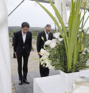 昨年9月の北海道地震で被害を受けた厚真町吉野地区で、設置された献花台に花を手向け一礼する近藤泰行副町長(右)ら=8日