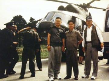 朝鮮人民軍のヘリコプターを前に写真に納まる朴采緒氏(右端)=1997年8月、北朝鮮・金剛山地区(朴采緒氏提供・共同)