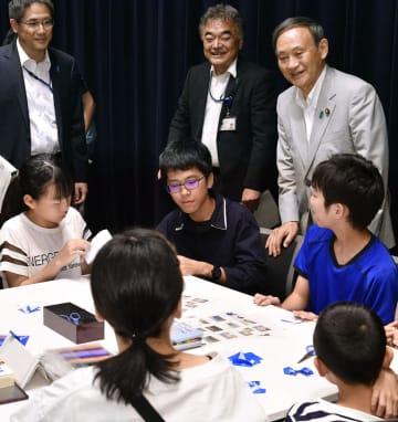 拉致問題解決を願うシンボルの「ブルーリボン」を折り紙で作る子どもたちに声をかける菅官房長官(右奥)=8日午後、東京・永田町