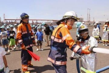 消防ホースを使って放水訓練を体験する児童