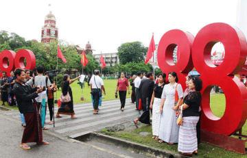 初めて屋外で行われた式典に集い、記念撮影する市民=8日、ヤンゴン(NNA)