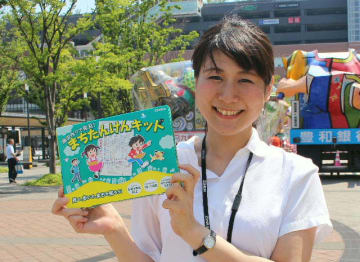 自身の発案で商品化された「まちたんけんキット」を手にするゼンリンの外池夏子さん=JR大分駅前