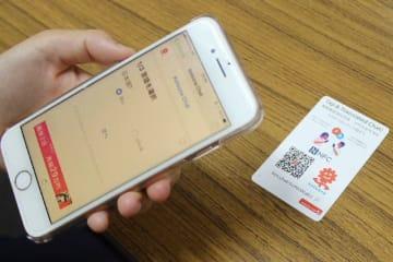 カードやQRコードにスマートフォンをかざして利用する翻訳システム