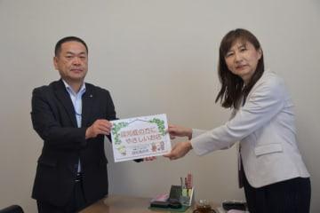 松川雄治支店長(左)にステッカーを手渡す斎藤晴美福祉部長