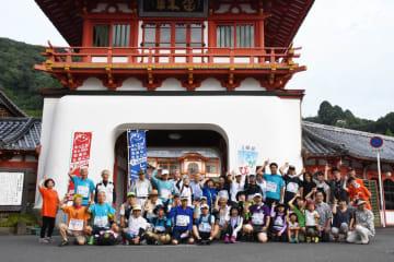 スタートの武雄温泉楼門前で記念撮影する参加者=武雄市武雄町