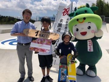 【スケートパーク来園1万人目の宮本君(左から2人目)に記念品を渡す竹上市長(左)=松阪市山下町で】