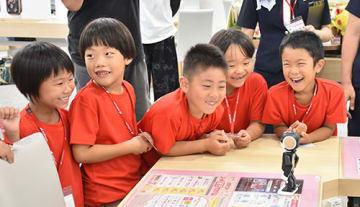 ロボット型携帯端末「ロボホン」(右手前)からあいさつを学ぶ子どもたち=山形市・ドコモショップ山形北店