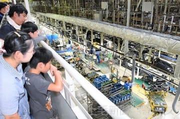 自動車の生産ラインを見学する参加者