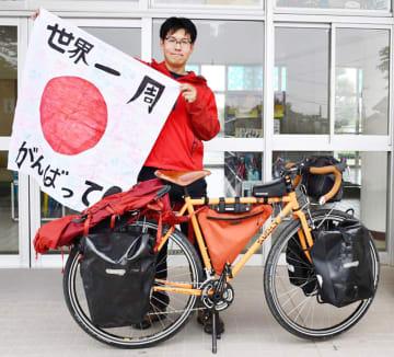 自転車世界一周旅行を前に児童から受け取った寄せ書きの旗を掲げ意気込んだ佐藤さん=昨年6月、印西市立木刈小学校
