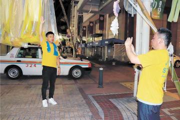 七夕飾りの安全確認で、夜間の保管状況を写真に収める自主警備部員=6日午後10時40分ごろ、仙台市青葉区一番町