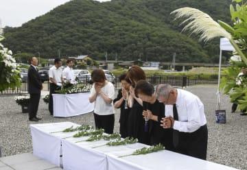 豪雨災害から10年となり、献花台で手を合わせる遺族ら=9日午前、兵庫県佐用町