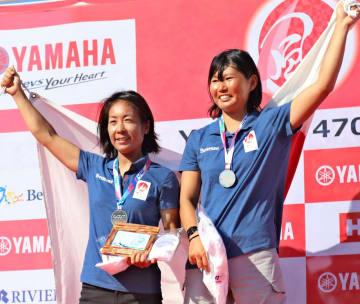 総合2位で東京五輪代表に内定し、表彰台で笑顔を見せる吉田(左)、吉岡組=藤沢市の江の島ヨットハーバー