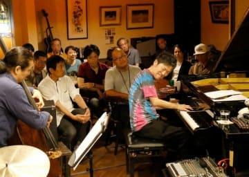 音をかみしめるように演奏する石井さん(中央)=7月11日