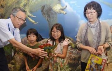 祖母と弟と一緒に訪れ、近藤館長から3万人目の記念品を受け取る牛田希実さん(中央)