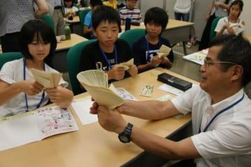 模擬紙幣を使って札束の勘定に挑戦する児童たち