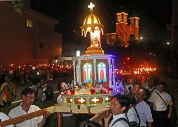 「被爆マリア像」を中心に光の帯をつくったたいまつ行列=9日午後8時5分、長崎市橋口町