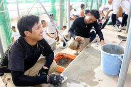 野球部員が着替えなどに使うグラウンド脇の観覧席で、ひび割れを補修する馬渡将平さん(左)と上原裕樹さん=明石市魚住町長坂寺