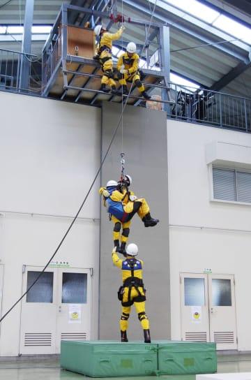 ヘリの機体を模した装置を使い、つり上げ救助の訓練を行う群馬県防災航空隊員=6月、前橋市