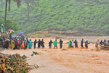 9日、インド南部ケララ州の洪水現場で、地元住民らを誘導する救助隊(ロイター=共同)