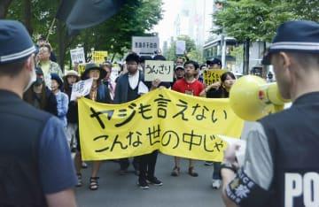 垂れ幕などを手に、北海道警に抗議する人たち=10日午後、札幌市