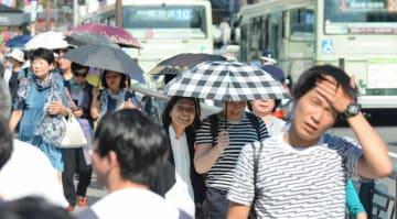 今夏最高気温を記録する暑さとなり、照りつける日差しを日傘でしのぐ人たち(10日午後3時24分、京都市・四条大橋)