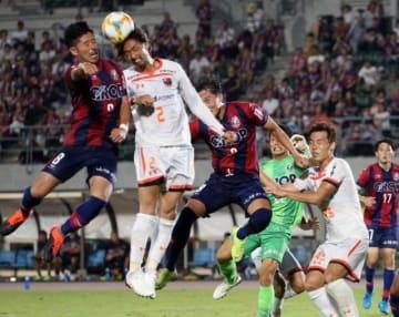 後半ロスタイム、CKからゴールを狙ってファジアーノ岡山の田中裕介(左)が飛び付くが相手に阻まれる=シティライトスタジアム