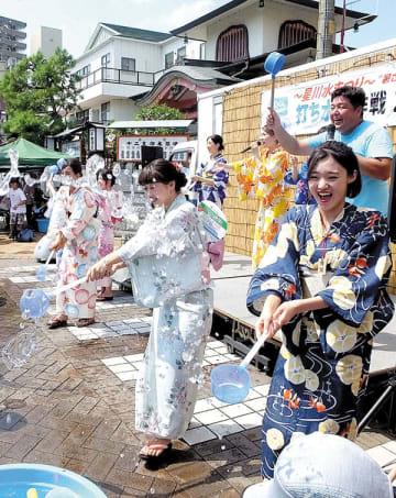 ひしゃくを使って、たらいに入った水を一斉にまく参加者ら=10日午後、熊谷市の星川通り
