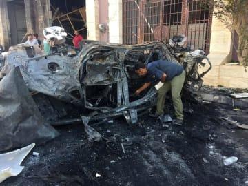 10日、リビア東部ベンガジで、自動車爆弾が爆発した現場を調べる治安当局者(ロイター=共同)