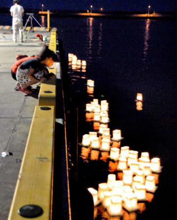 松川浦漁港に放たれた灯籠を眺め、鎮魂を祈る子どもたち