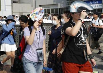 強い日差しをうちわなどで遮りながら歩く人たち=11日午後、東京都江東区