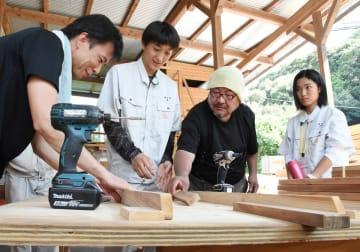 従業員に教わりながら、椅子を製作する高校生たち=佐賀市富士町の黒田木材商事の工場