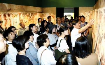 キジル石窟の壁画を解説する井上隆史特任教授(手を上げている男性)=8月11日、福井県福井市の県立美術館