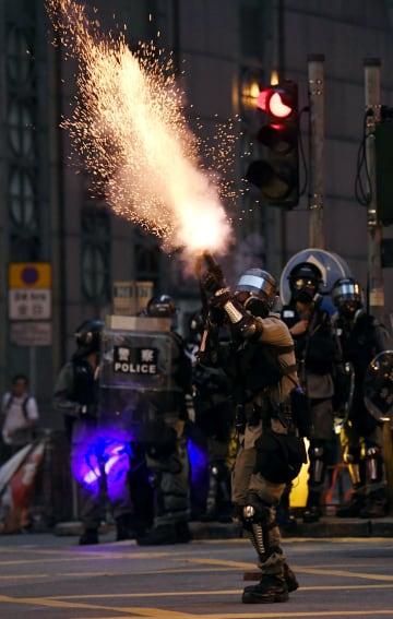 香港島で、デモ隊に向け催涙弾を発射する警官隊=11日(共同)