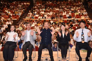 会場で観衆らと記念写真に収まる野口さん(中央)=茅ケ崎市民文化会館