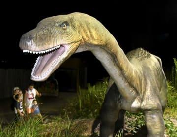 ライトアップされた動く恐竜ロボットの迫力に驚く家族連れ=8月10日夜、福井県勝山市のかつやまディノパーク
