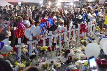 米テキサス州エルパソで起きた銃乱射事件の現場近くで犠牲者を悼む人々=6日