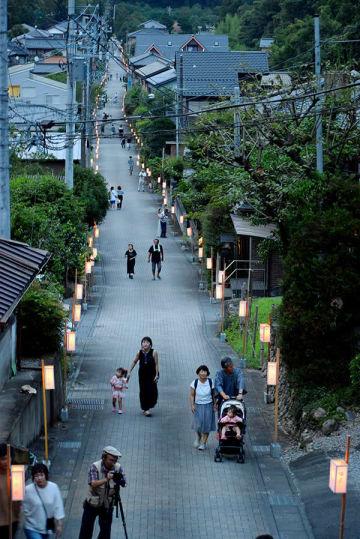 岩殿観音(正法寺)の参道にともされた灯籠の中を歩く参拝者=9日、東松山市岩殿