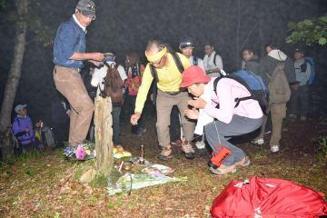火の玉探検で山頂付近に到着し、「お釈迦様の墓」に線香を手向ける参加者たち