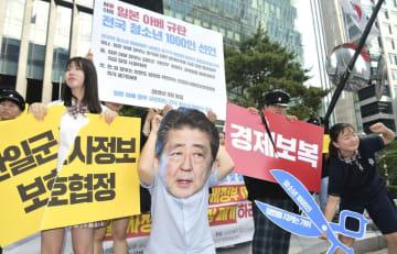 「経済報復」などと書かれた紙を細断するパフォーマンスを行い、日本の輸出規制強化に抗議する韓国の若者ら=10日、ソウル(共同)