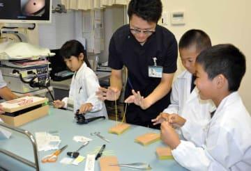医師から縫合する糸の結び方や内視鏡の使い方を教わる子どもたち(京都府京田辺市田辺・田辺中央病院)