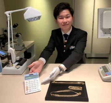 客が持ち込んだ金の装飾品を査定する鑑定士(コメ兵銀座店で、石原健太郎氏撮影)