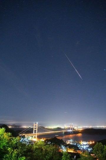 瀬戸大橋上空を流れるペルセウス座流星群。倉敷市下津井から南南東の空に向け、三島学芸員が撮影=12日午前2時19分