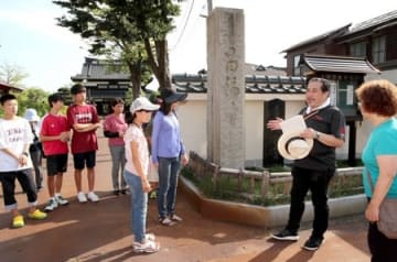 空襲犠牲者の遺骨が埋葬された昌福寺を訪れ、当時に思いをはせる参加者ら=11日、長岡市