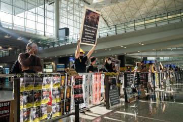 13日、香港国際空港で、香港当局への抗議を示すプラカードを持つ人ら(ゲッティ=共同)