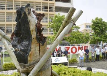 沖縄国際大に米軍ヘリコプターが墜落した事故から15年となり、焼けたアカギの木が残る現場跡地で開かれた集会=13日午後、沖縄県宜野湾市