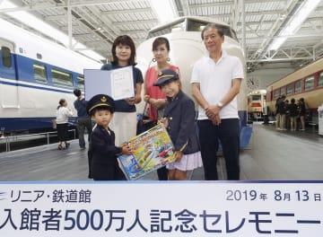 「リニア・鉄道館」の500万人目の入館者となり、記念品を贈られた高田知穂さん(後列左)一家=13日、名古屋市