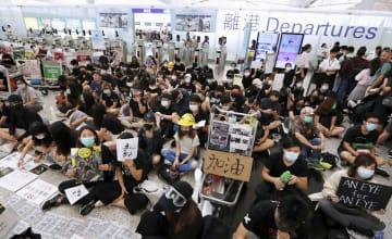 「逃亡犯条例」改正案を巡り、香港国際空港の出発ゲート前に座り込むデモ隊=13日(ロイター=共同)